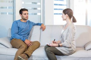 man talking to counselor and receiving addiction therapy
