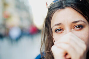 young woman with hands clasped in front of face considers addiction rehab