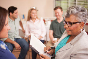 older woman leading group therapy at an alcohol detox center
