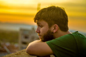 man staring over city at sunset has opiate addiction