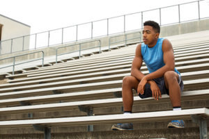 athlete sitting on bleachers struggling with prescription drug abuse