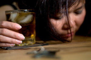Asian woman with drink has alcohol poisoning