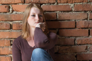 woman sitting against brick wall with head in hand wants to know how to quit heroin