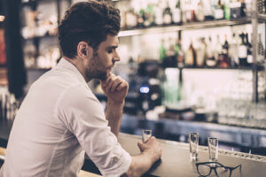 man sitting at the bar exhibits symptoms of alcoholism