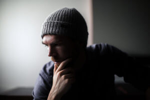 man with beanie in dark room shows signs of alcoholism
