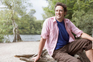 man sitting by lake participates in addiction treatment aftercare