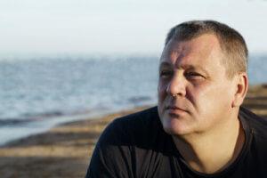 middle-aged man on the beach has alcohol addiction