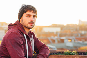man in hoodie overlooking city goes through alcohol withdrawal stages