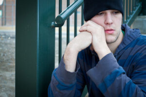 young man sits on step and contemplates drug addiction treatment