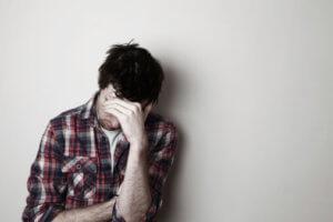 man sitting against a wall has meth addiction