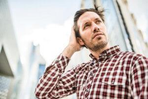 man with hand on head contemplates painkiller addiction treatment