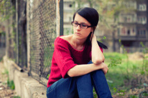 woman sitting on curb needs relapse prevention