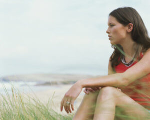 woman sitting on beach considers seeking addiction help