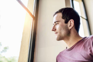 man looks out the window of a sober living home