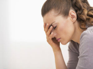 woman with her head in her hands going through oxycodone withdrawal
