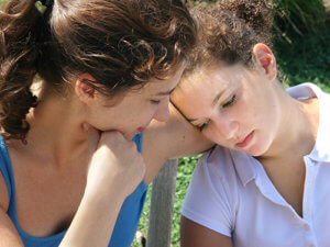 A girl struggling with addiction leans on her sister's shoulder during family counseling.