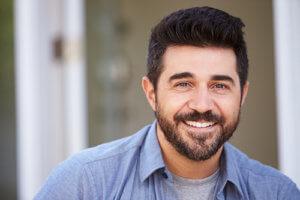 A man smiles while in men's drug rehab