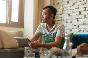 man with ipad researches rehab centers