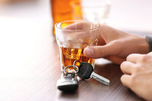 A pair of car keys lie ominously next to a shot of whiskey while the user remains unaware of DUI vs DWI