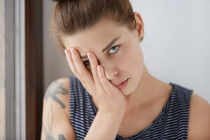 A woman worries appears stressed while wondering why do addictions occur