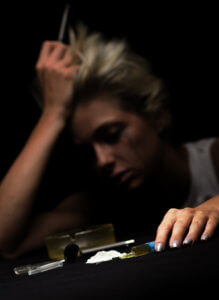 A woman exhibits signs of cocaine use